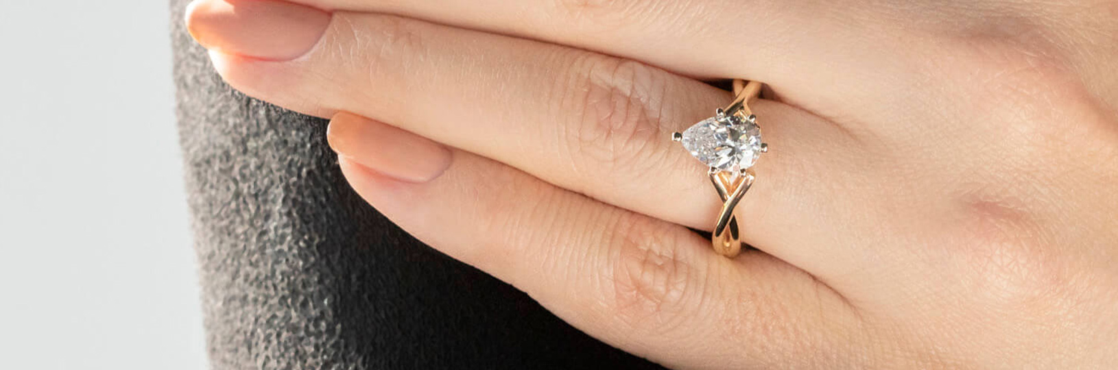 A pear shaped engagement ring with a twisted band