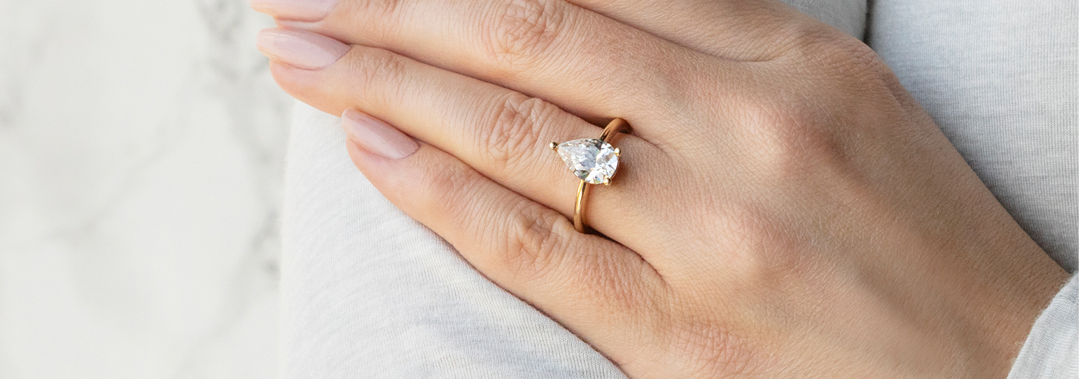 A pear cut stone in a solitaire engagement ring setting