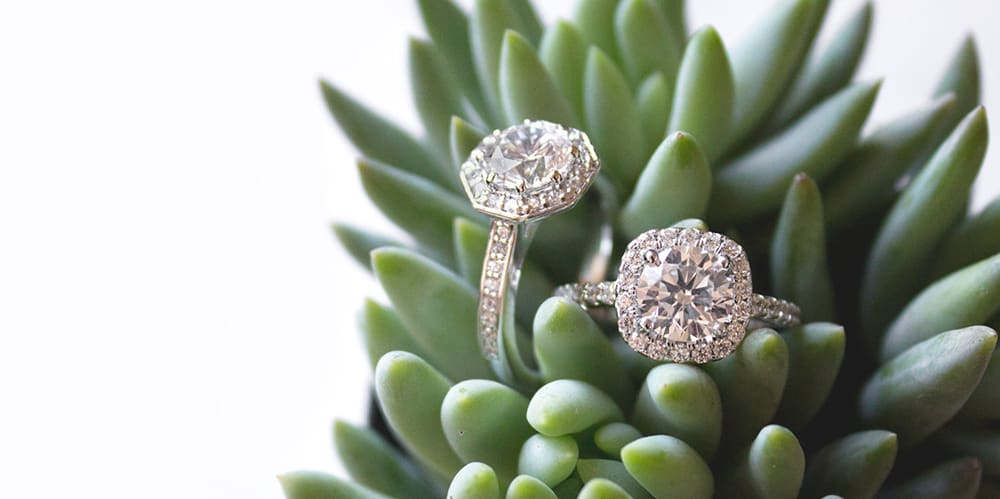 Two halo engagement rings set with Nexus Diamond™ alternatives.