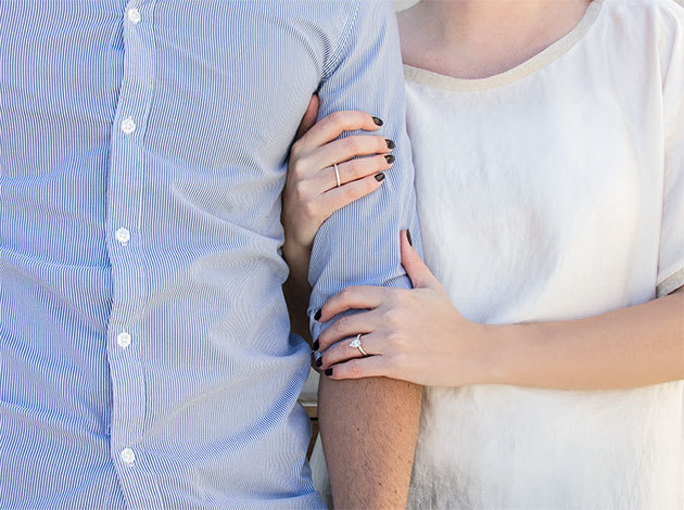 A couple holding hands featuring a solitaire Diamond Nexus engagement ring.