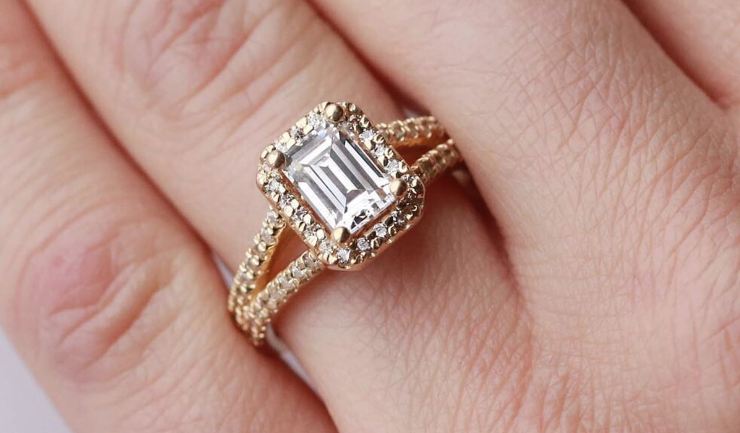 A Diamond Nexus halo Emerald cut engagement ring in yellow gold.