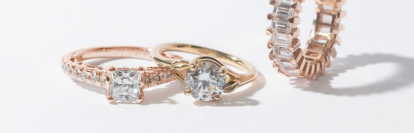 Three Diamond Nexus engagement rings in yellow and rose gold.