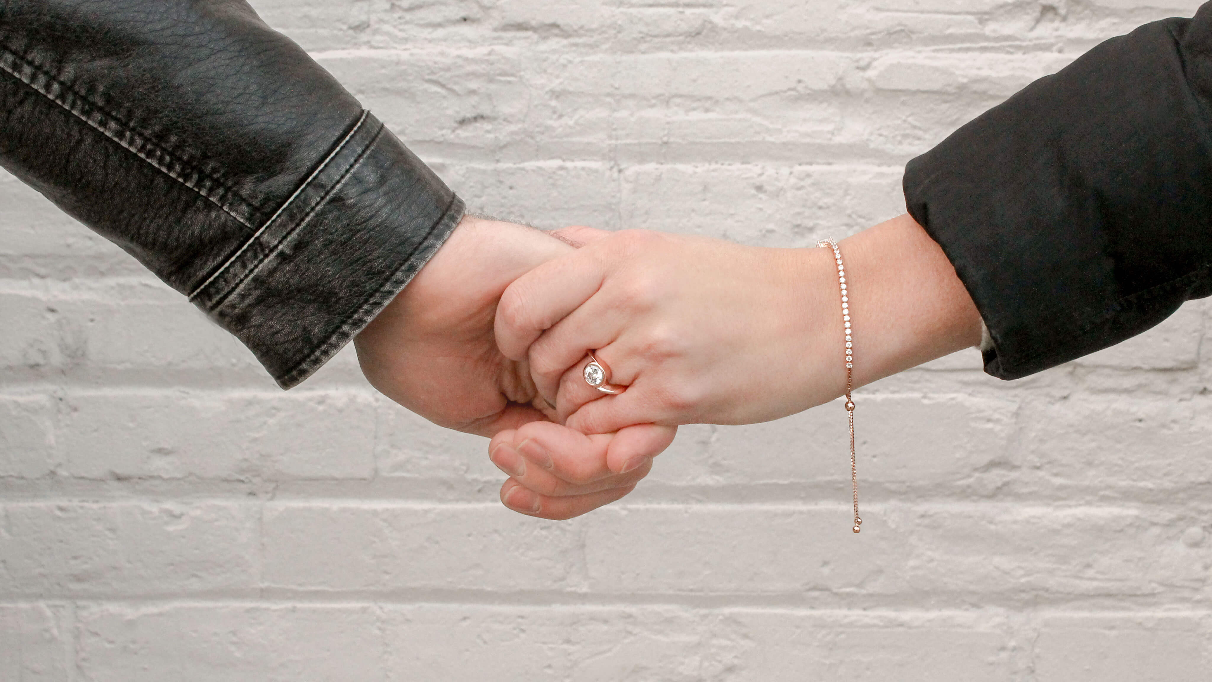 Bound to You Radiant Cut Bracelet and Round cut engagement ring in rose gold, featured on a couple holding hands.