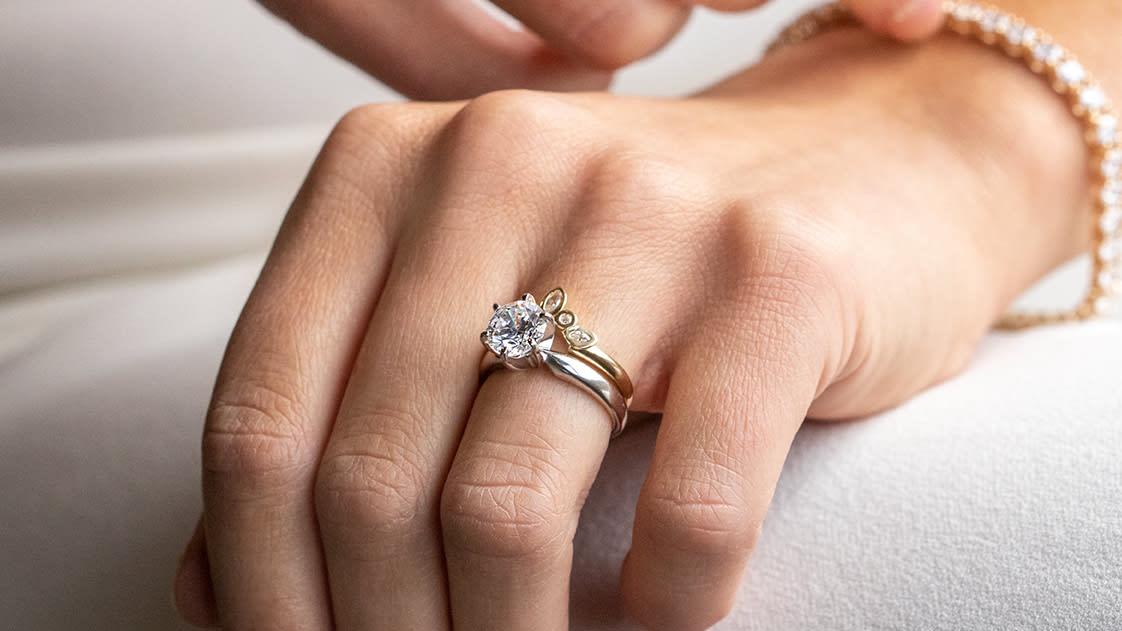 A close-up of a bride wearing a Diamond Nexus wedding ring set and tennis bracelet.
