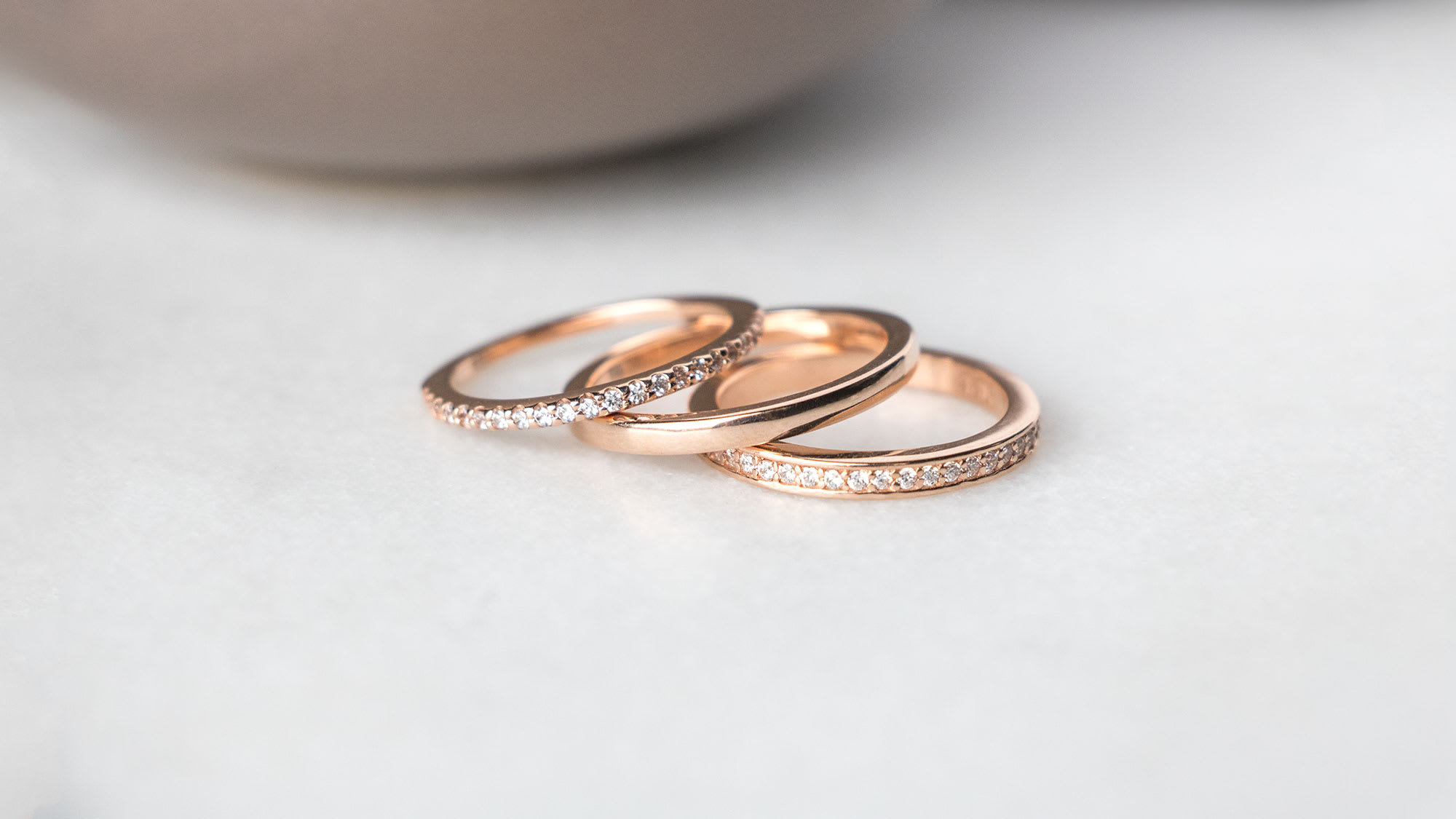 A rose gold ring stack featuring three Diamond Nexus bands.