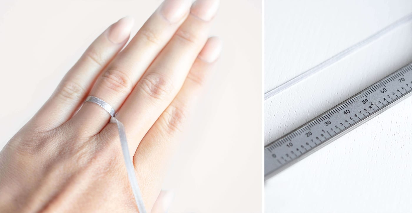 Ribbon being tied around a finger to determine ring size then placed next to a ruler.