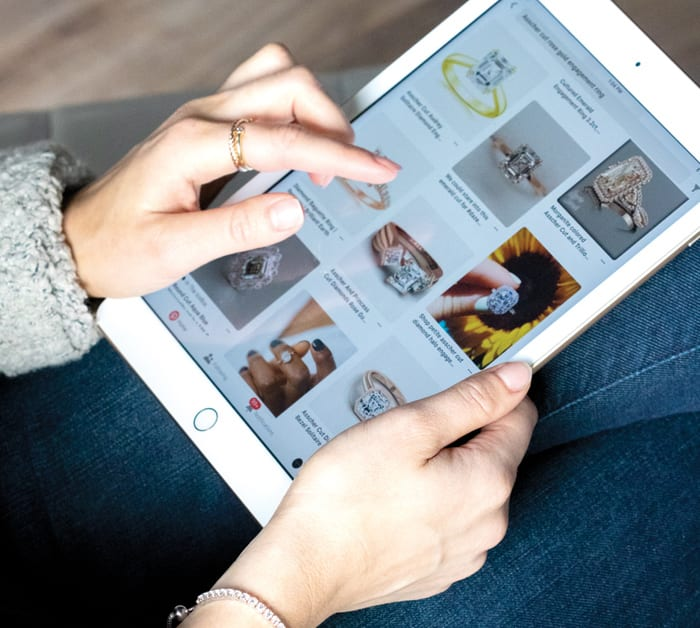 woman researching engagement ring options on a tablet