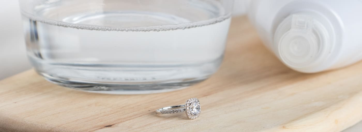 A Diamond Nexus engagement ring next to a bowl of mild soap and warm water