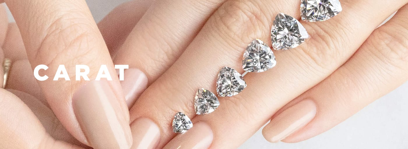 Loose Trillion cut Nexus Diamond alternatives in various carat weights resting on a hand