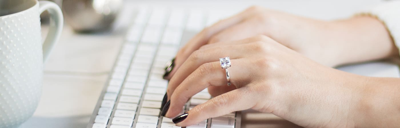 Solitaire engagement ring from Diamond Nexus featured on a hand typing on a keyboard