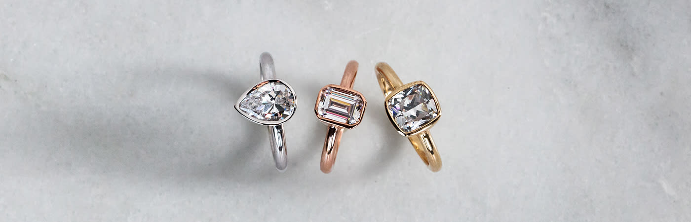 Three solitaire engagement rings in yellow, white and rose gold from Diamond Nexus