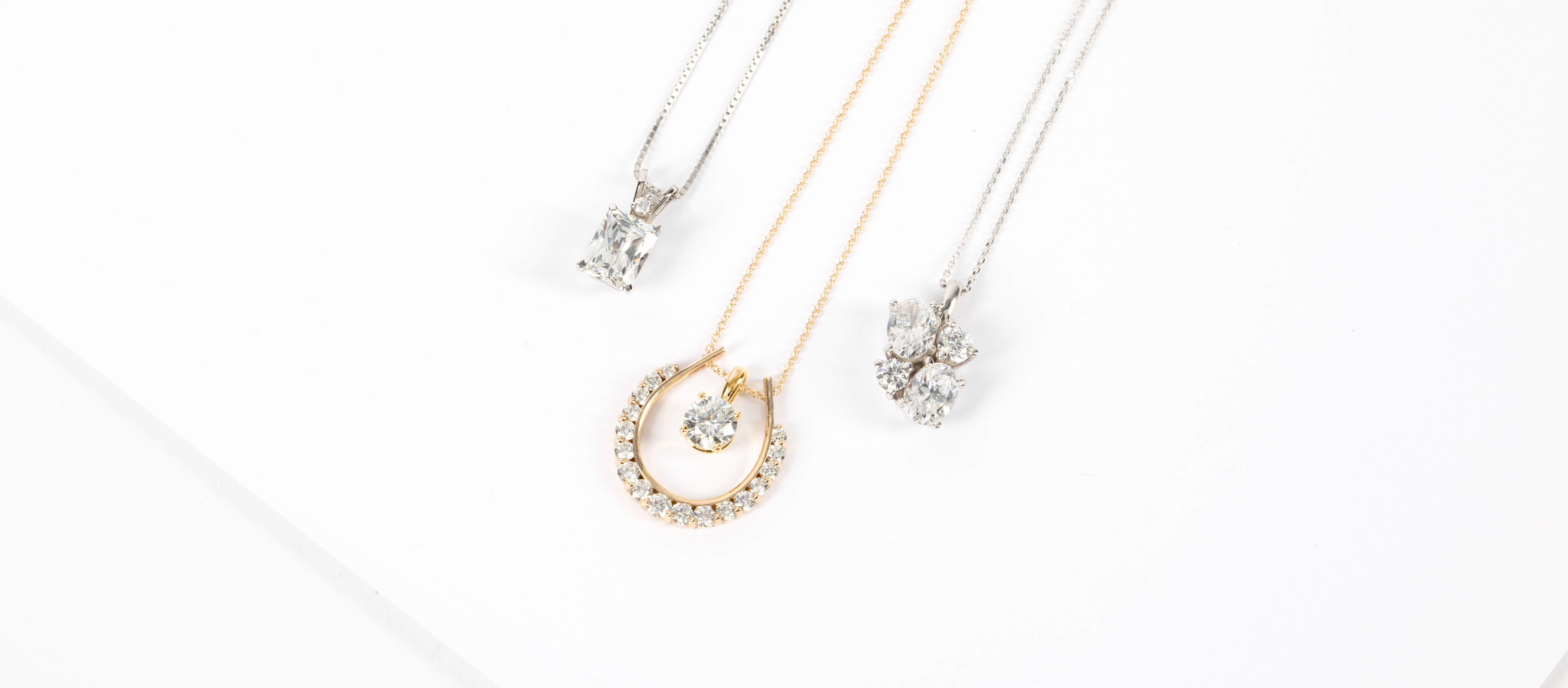 Assorted Diamond Nexus necklaces in white and yellow gold.