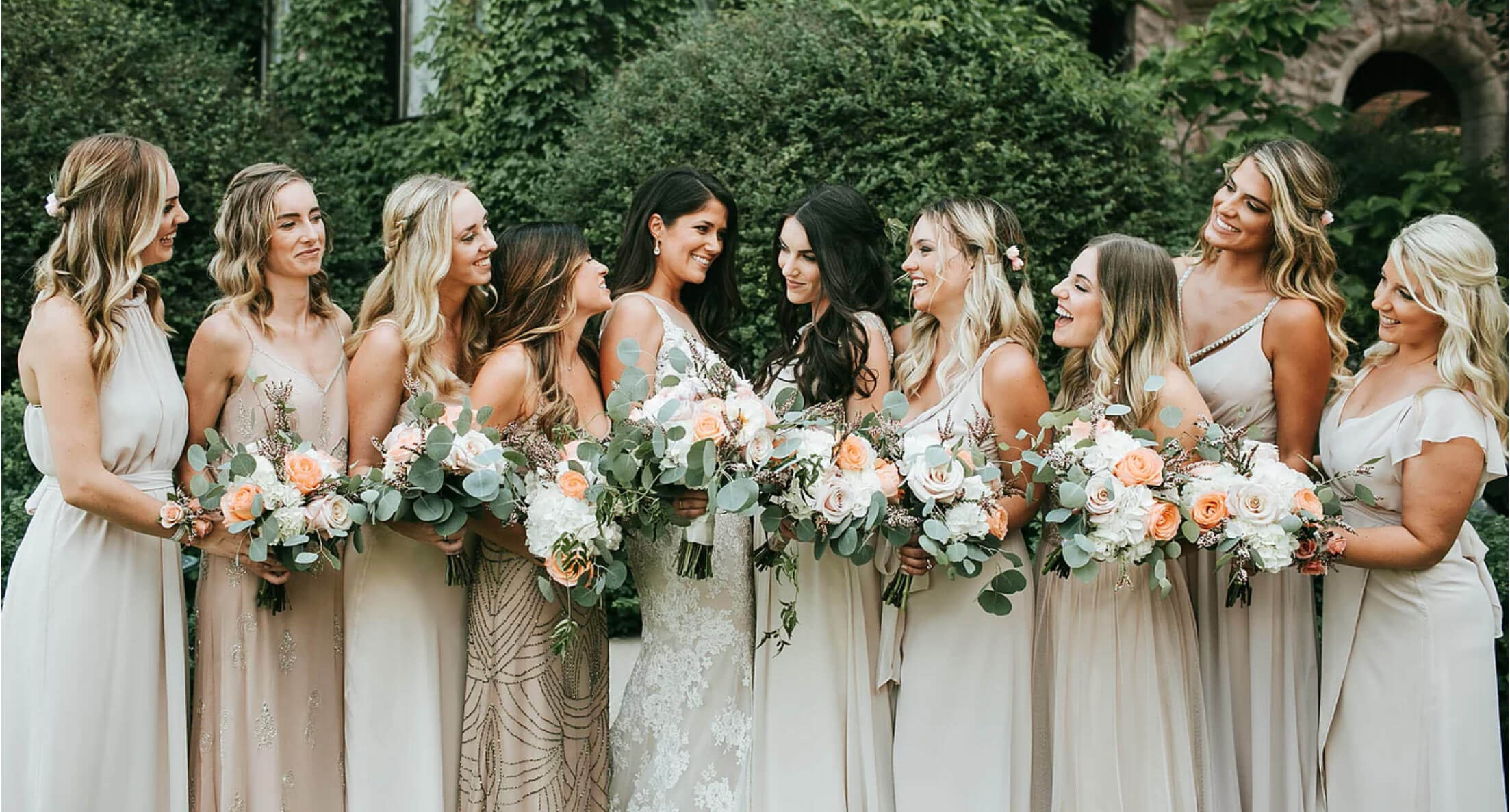 A bridal party holding bouquets admiring the bride.