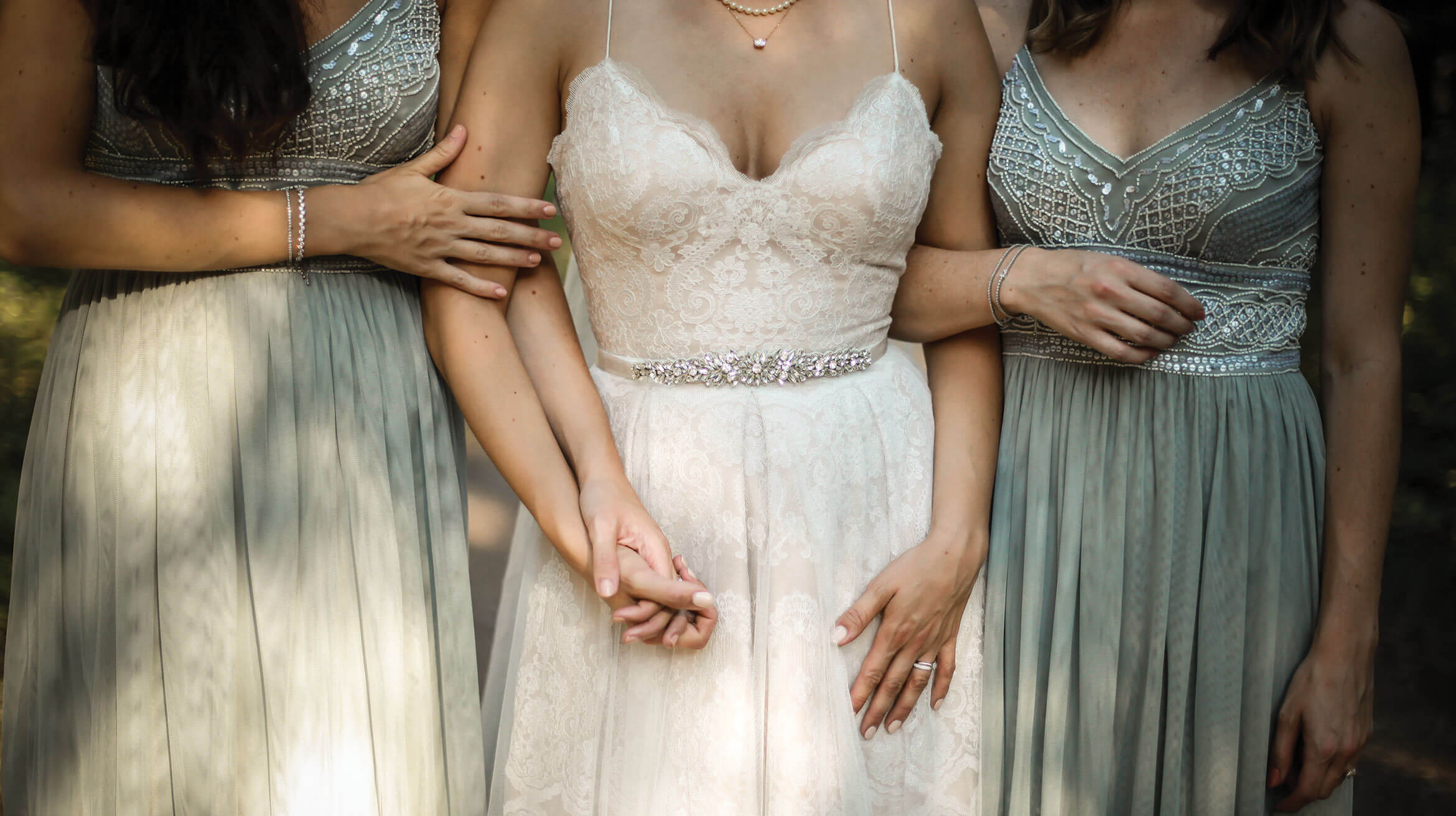 A bride and two bridesmaids holding hands before the ceremony.