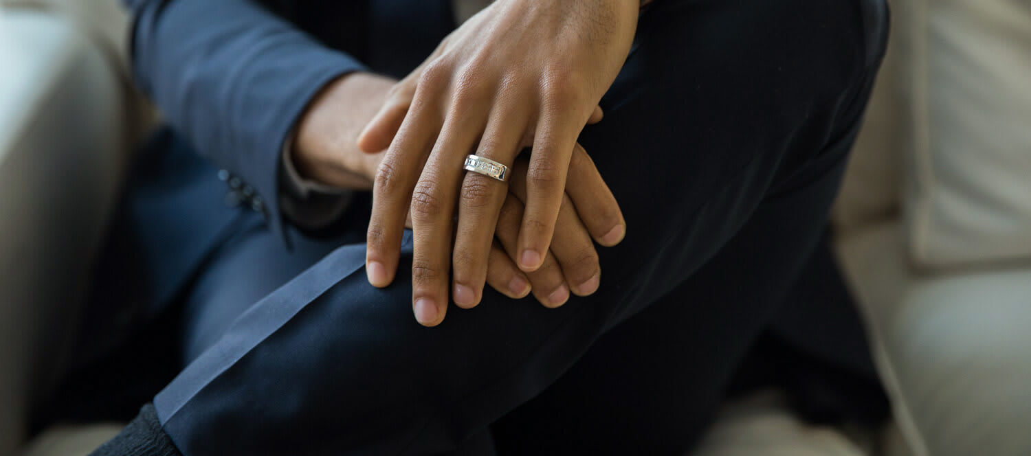 Man wearing an accented wedding band.