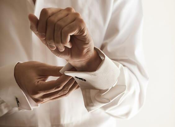 A groom fastening his cufflinks.