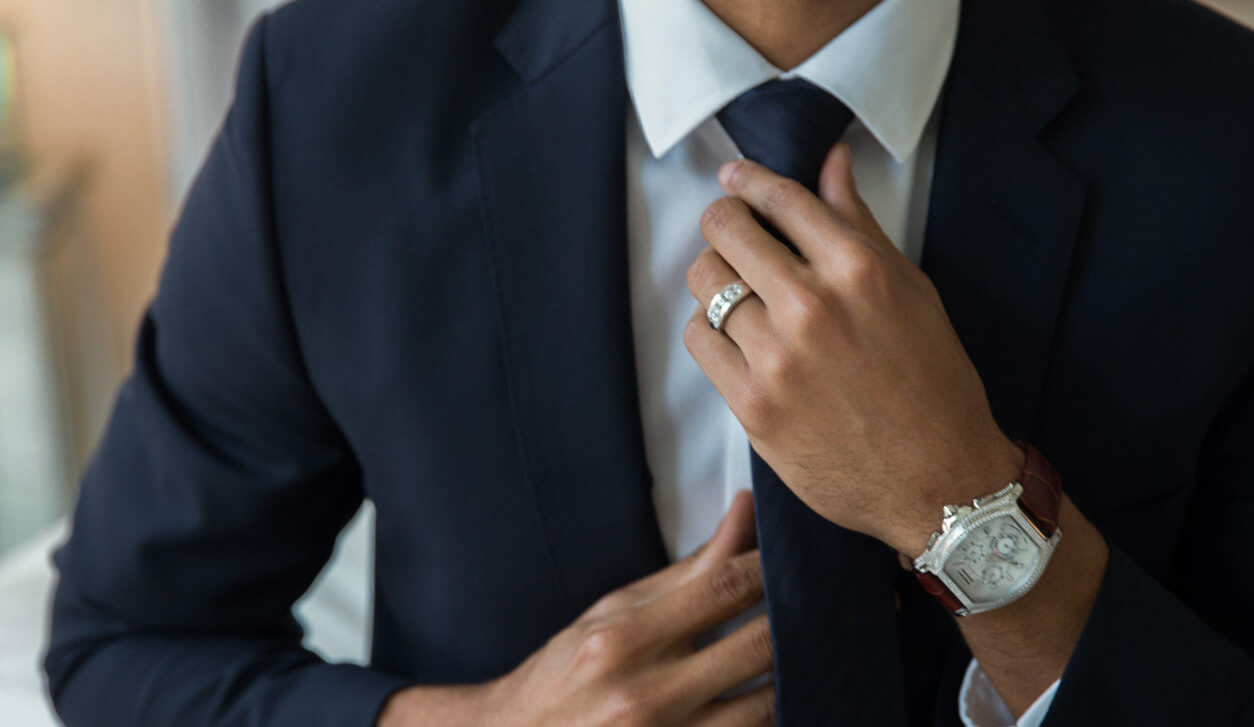 Man wearing a wedding band and luxury watch.