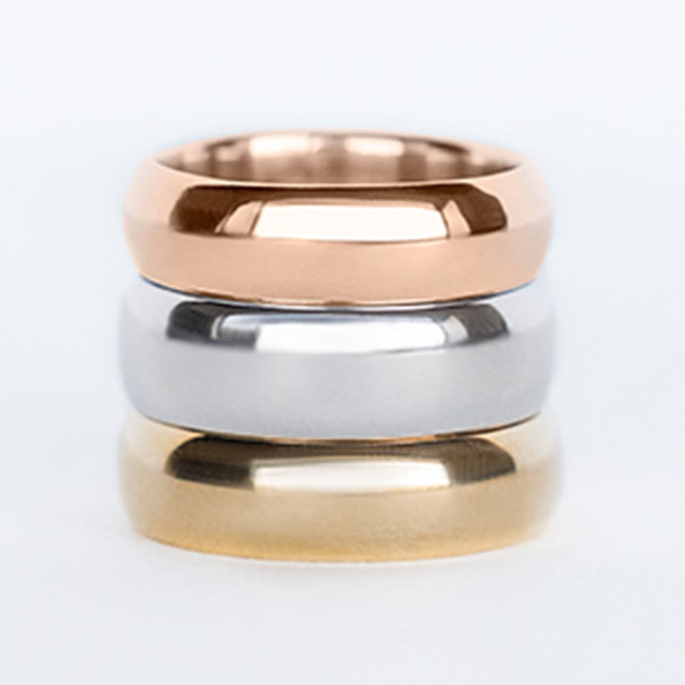 A rose, white and yellow gold wedding band stacked on top of each other.