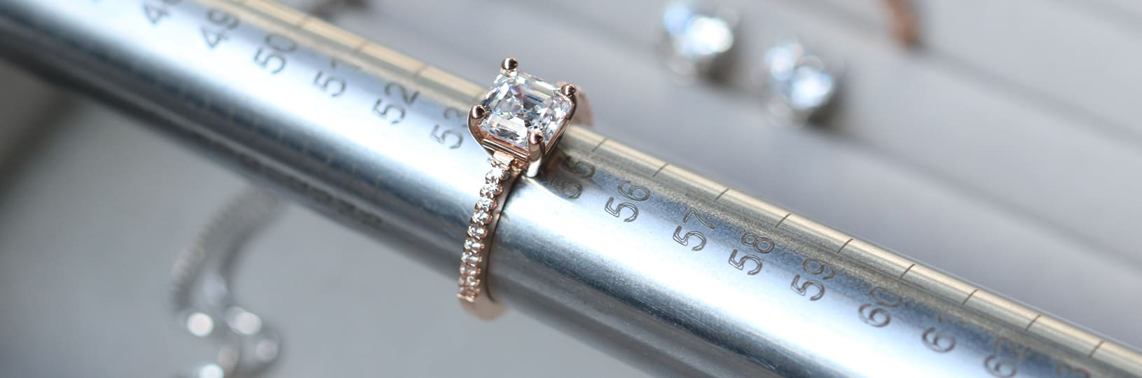 A lab created diamond simulant engagement ring being measured on a mandrel.