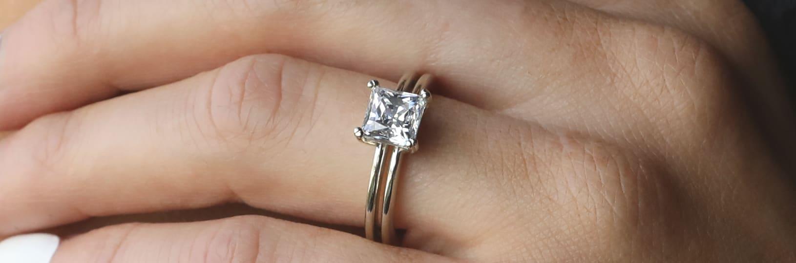 Two bezel set lab created diamond simulant engagement rings.