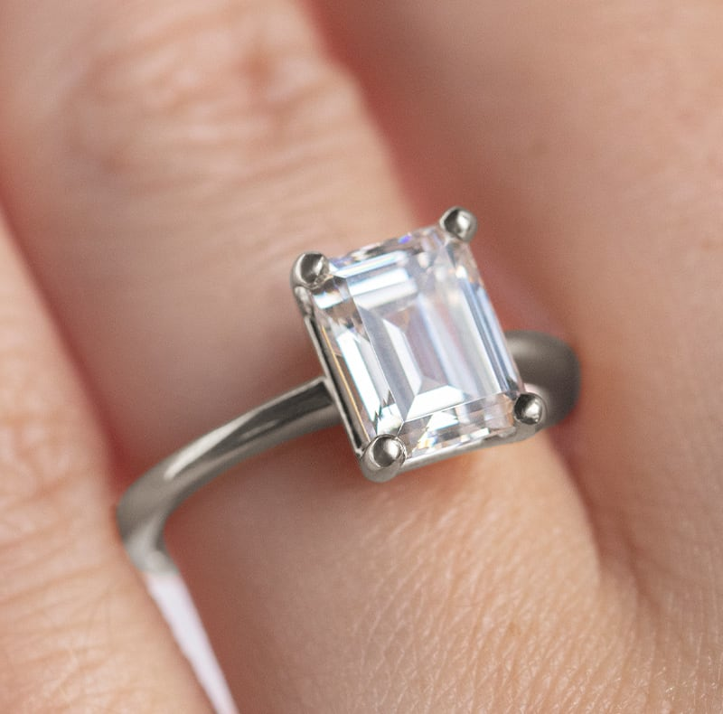 An emerald cut stone fixed to a solitaire band