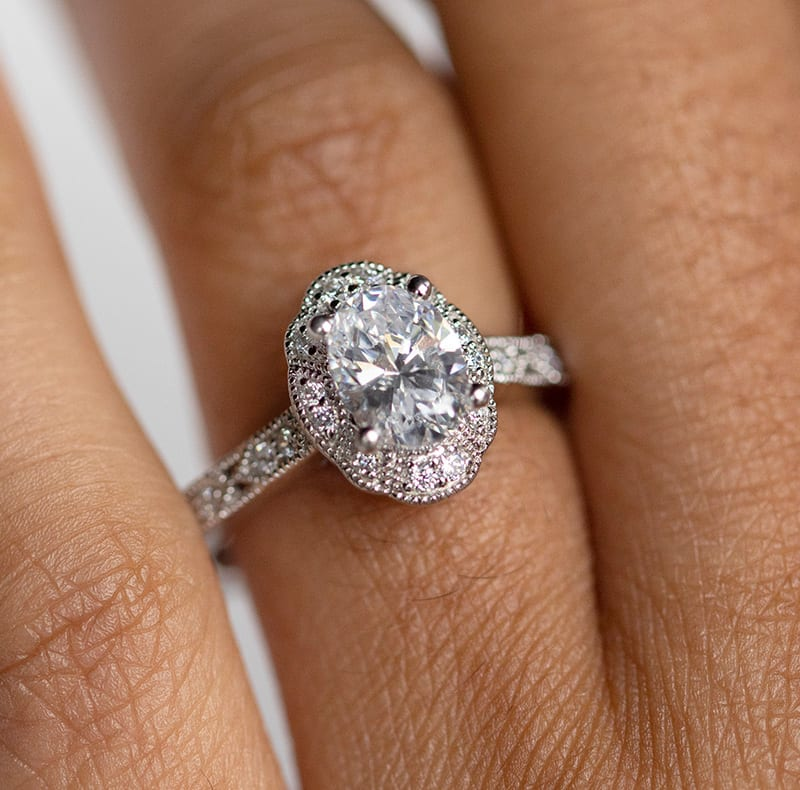 An oval cut stone in a vintage halo engagement ring setting