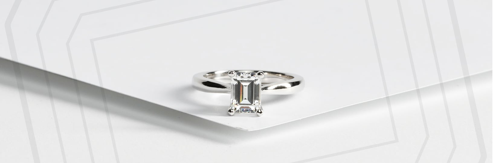 An emerald cut stone with a silver solitaire settings