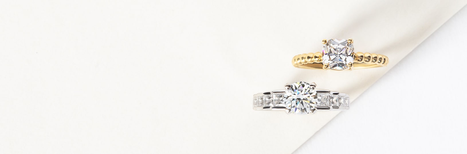 A yellow gold and white gold engagement ring compared side by side