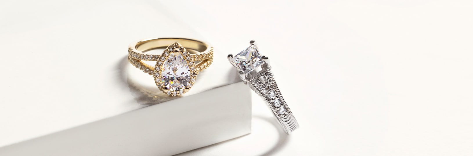 A pear cut yellow gold engagement ring and a princess cut white gold engagement ring pictured together