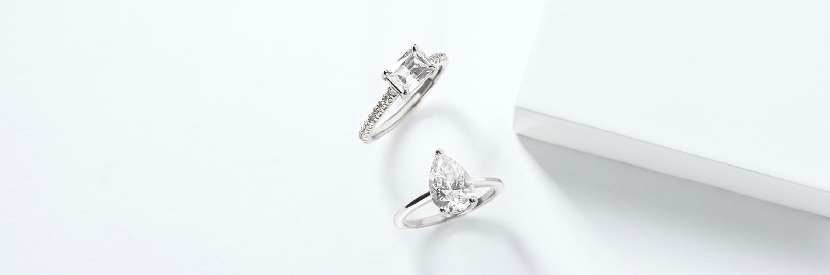 A baguette cut engagement ring with an accented band and a pear cut diamond alternative with a solitaire band