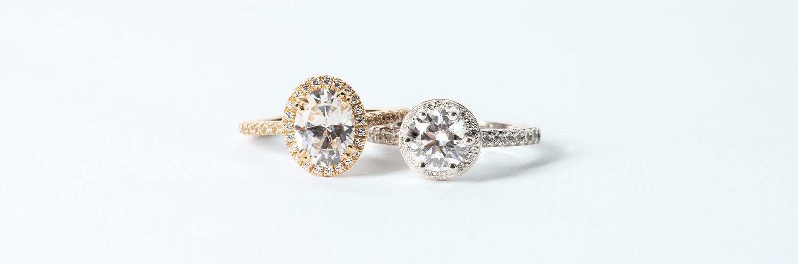 An oval cut simulated diamond and round cut simulated diamond pictured side by side