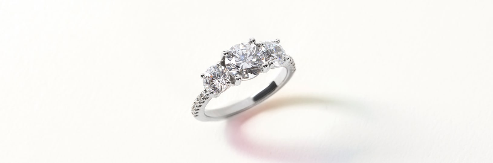 Three stone accented setting featuring round cut simulated diamonds