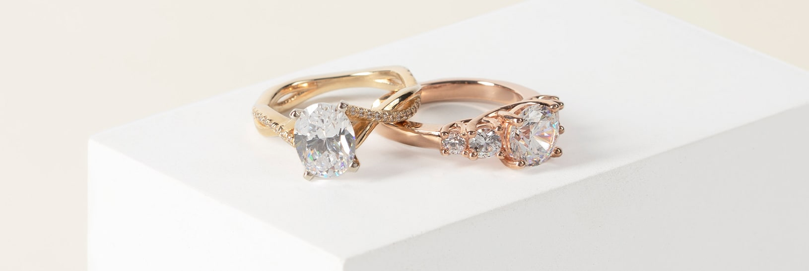 An oval and round cut simulated diamond in yellow and rose gold settings