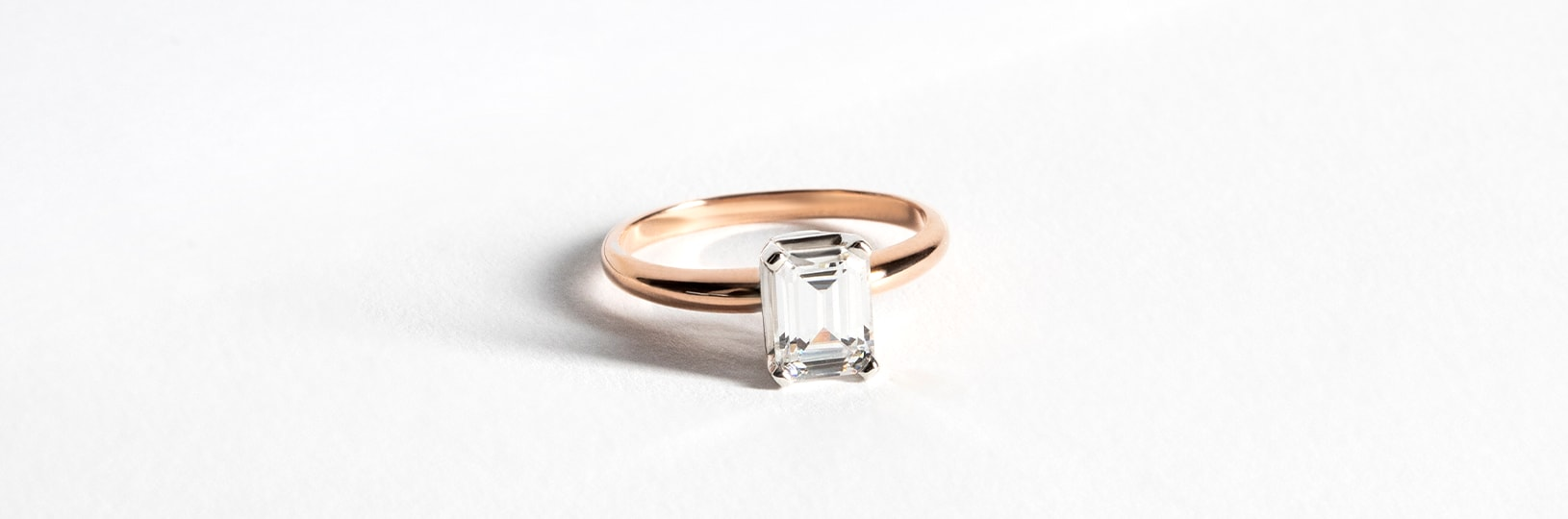A solitaire rose gold engagement ring with an emerald cut stone