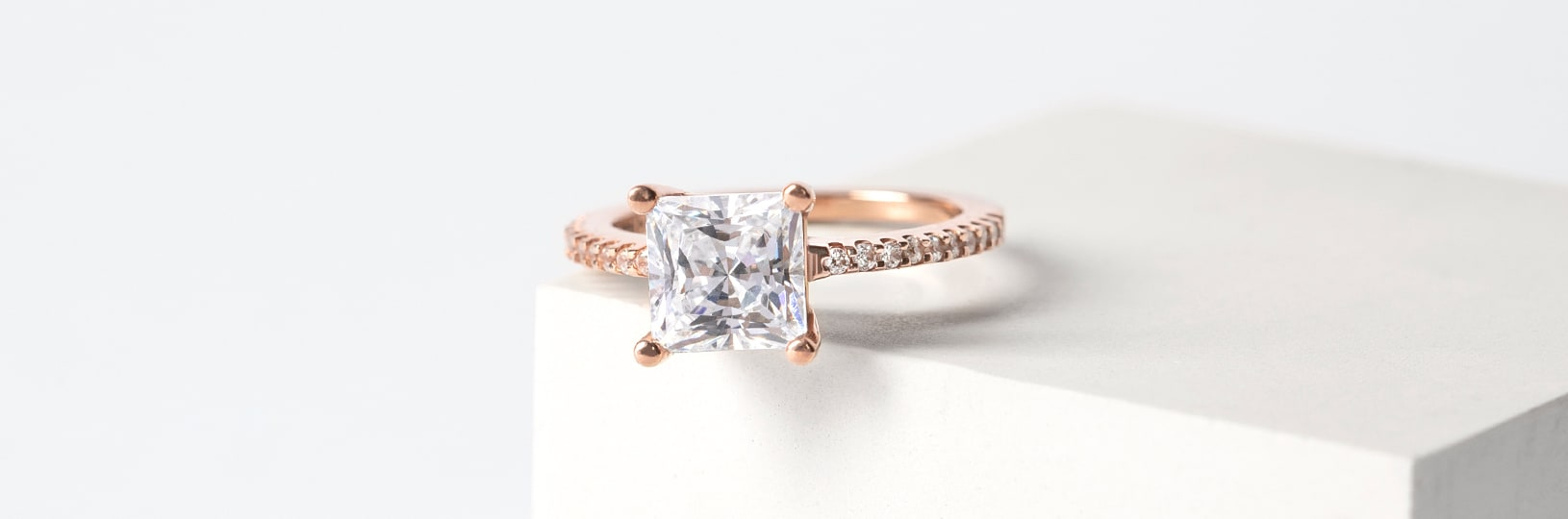 A rose gold engagement ring with an accented band