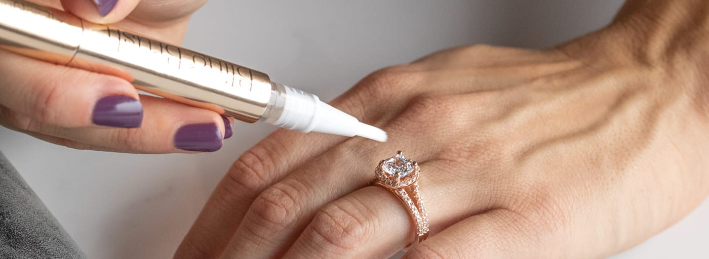 A person cleaning their rose gold ring