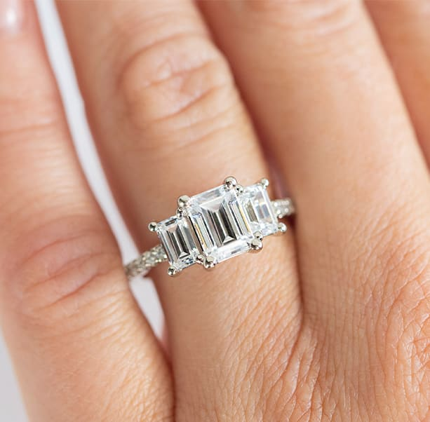 An engagement ring featuring an emerald cut center stone with two emerald cut side stones