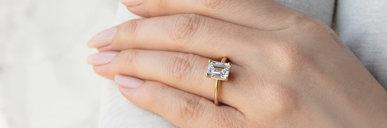 A solitaire setting with an emerald cut center stone