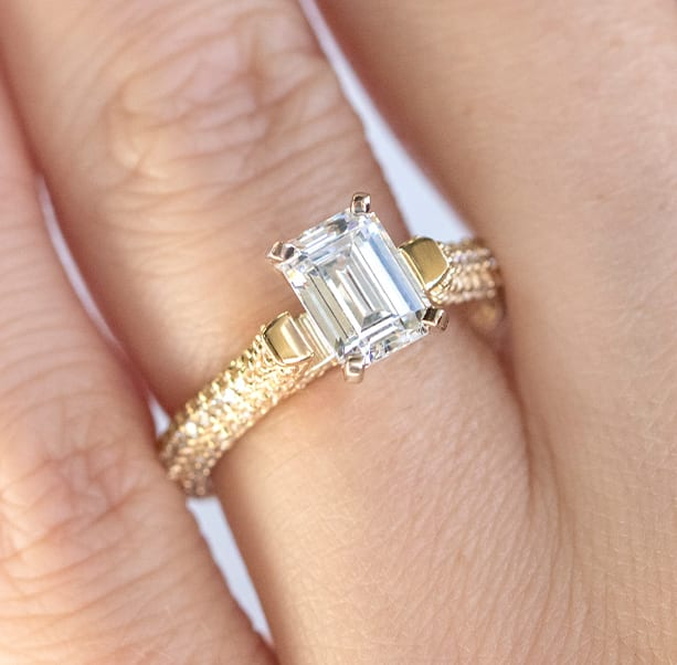 An emerald cut stone in a pave engagement ring setting