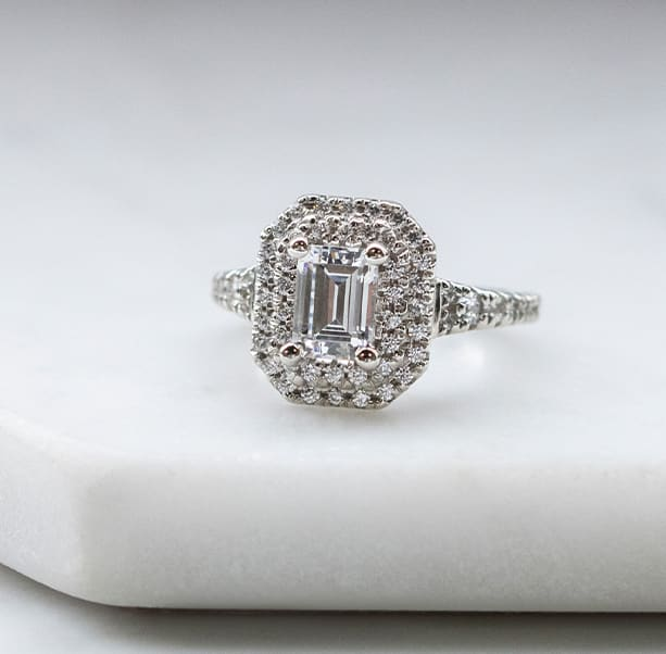 An emerald cut stone in a halo engagement ring setting