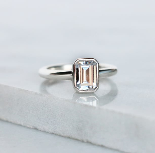 An emerald cut stone in a bezel engagement ring setting