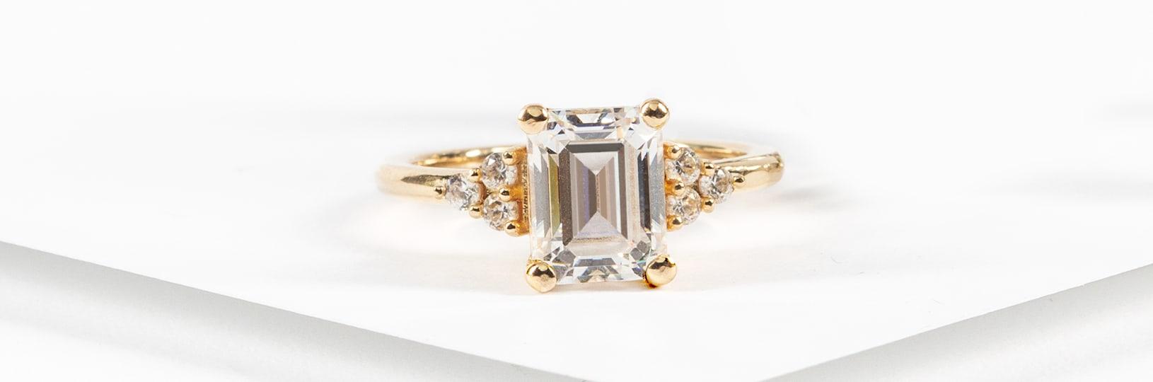 An engagement ring featuring an emerald cut center stone