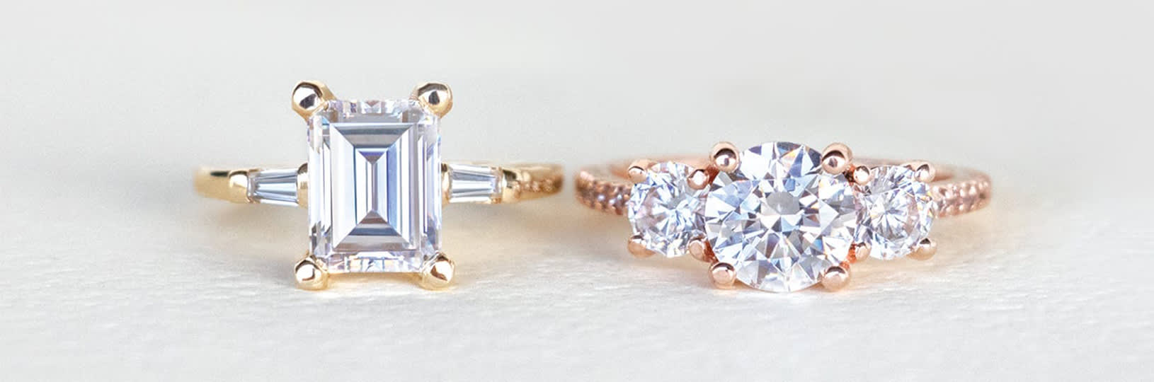 An emerald cut engagement ring in a three stone setting and a round brilliant cut engagement ring in a three stone setting