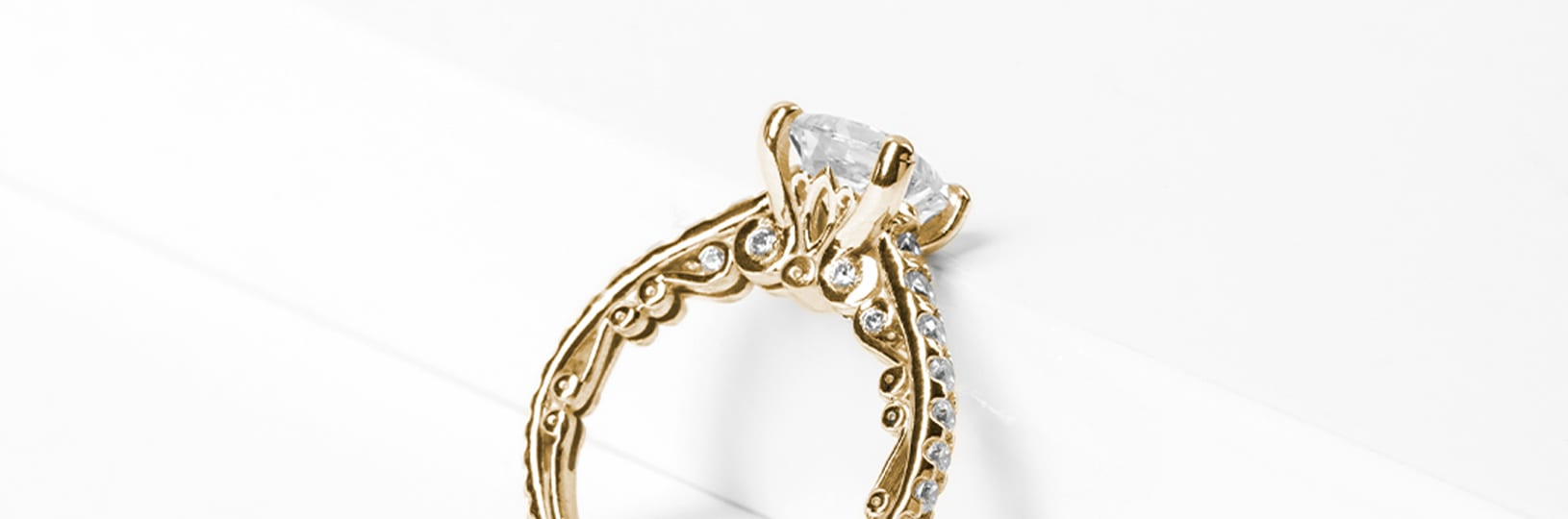 A yellow gold engagement ring with filigree
