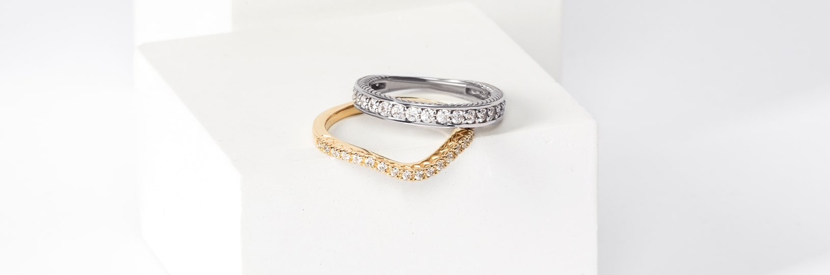 Two wedding bands, one in yellow gold, the other in white gold